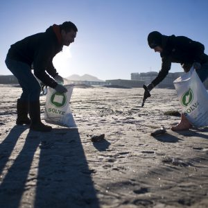 Photo by Alex Pajunas Guilibaldo Gonzalez, left, of Newberg, and his wife, Wendy, stoop to pick up garbage, including a sock, during the city of Seaside's Treasure the Beach Cleanup on a brisk January morning in Seaside.